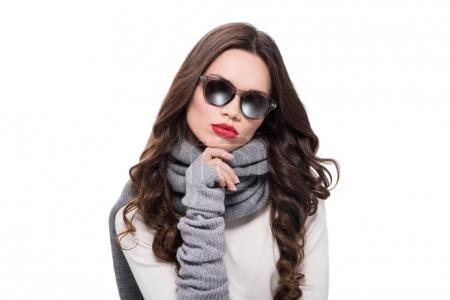 Photo for Young pretty woman in scarf and arm warmers, wearing trendy sunglasses and posing with hand on chin, isolated on white - Royalty Free Image