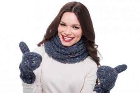 Photo pour Jeune femme heureuse en écharpe et mitaines montrant les pouces vers le haut, isolé sur blanc - image libre de droit