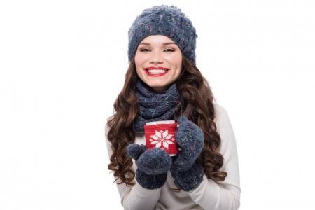 Woman in winter attire holding mug