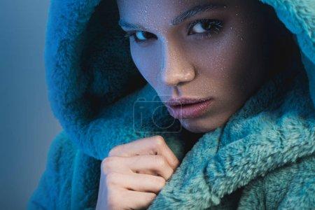 Foto de Toma de retrato de una mujer joven cubierto de escarcha y envuelto en la capa de piel verde - Imagen libre de derechos