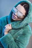 Woman in fur coat and sunglasses