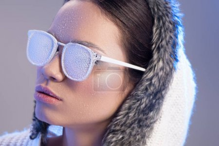 Photo for Portrait shot of a young woman covered in frost wearing sunglasses and sweater with hood - Royalty Free Image