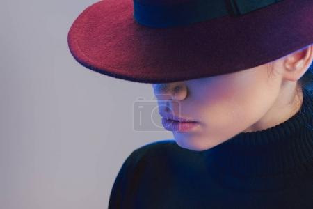 Photo for Young beautiful woman wearing burgundy wide-brimmed hat covering her face - Royalty Free Image