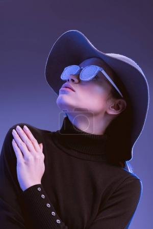 Model in wide-brimmed hat and sunglasses