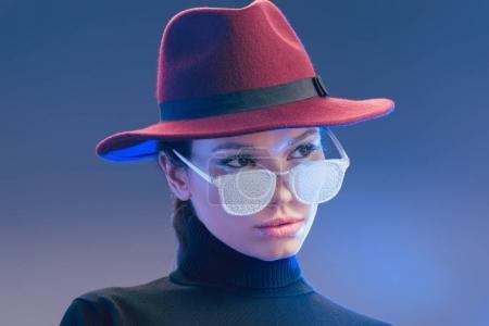 Photo pour Jeune femme séduisante portant un chapeau bordeaux à large bord regardant au-dessus des lunettes de soleil couvertes de gel - image libre de droit