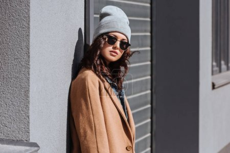 Photo pour Portrait de femme séduisante en tenue d'automne et lunettes de soleil noires debout dehors et regardant la caméra - image libre de droit