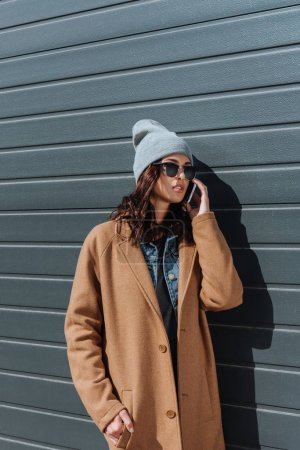 Photo pour Attrayant femme en tenue d'automne et lunettes de soleil noires parler par smartphone à l'extérieur - image libre de droit