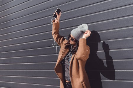 Woman in autumn outfit listening to music