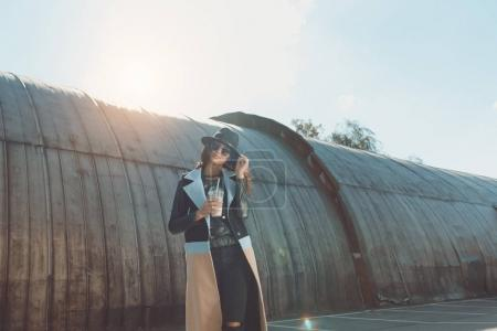 Woman in autumn outfit standing with milk shake