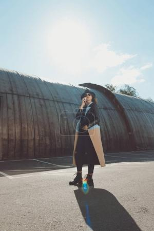 Woman in autumn outfit talking by smartphone