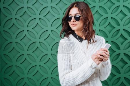 Woman in sweater and sunglasses listening to music