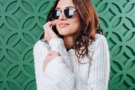 Photo pour Belle femme en pull blanc d'hiver et lunettes de soleil noires parlant par smartphone sur vert - image libre de droit