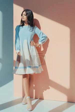 Photo pour Belle femme debout en robe turquoise à la mode avec des manches longues et détournant les yeux - image libre de droit