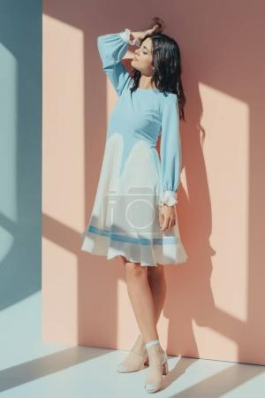 Woman in turquoise dress with closed eyes