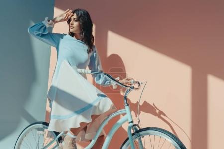 Photo pour Belle femme debout dans une robe turquoise à la mode avec des manches longues et assis sur le vélo et à la recherche de quelqu'un - image libre de droit