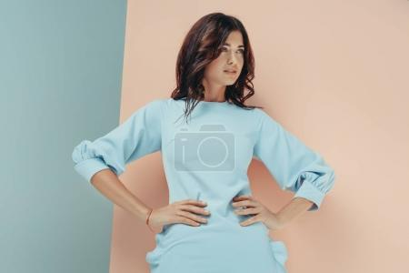 Photo for Stylish woman standing in fashionable turquoise dress looking away - Royalty Free Image