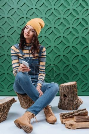 Woman sitting on stumps and listening to music