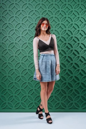 Woman in jeans skirt and orange sunglasses