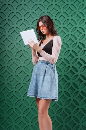 Woman in sunglasses looking at tablet computer