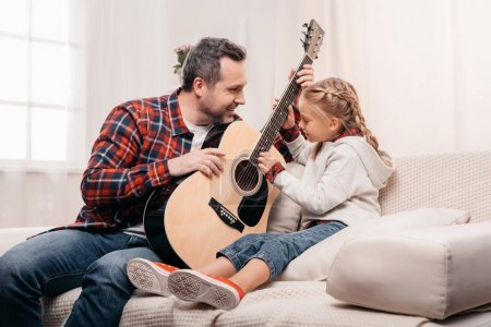 Photo for Happy father with adorable smiling little daughter playing guitar together at home - Royalty Free Image