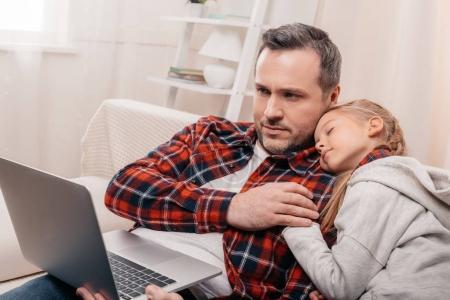 Photo pour Homme à l'aide d'ordinateur portable tout en mignonne petite fille dormir sur son épaule - image libre de droit