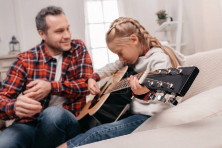 Photo for Happy father looking at cute little daughter playing guitar at home - Royalty Free Image