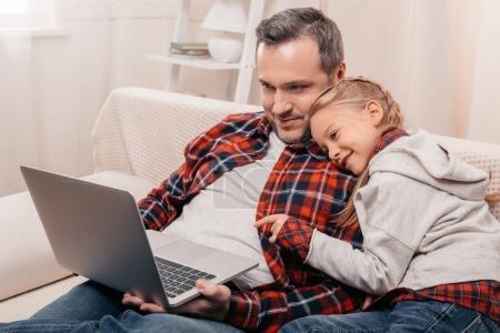 Photo pour Souriant, père et fille avec ordinateur portable ensemble à la maison - image libre de droit