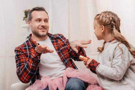 Photo pour Père heureux avec la mignonne petite fille polissage ongles ensemble - image libre de droit