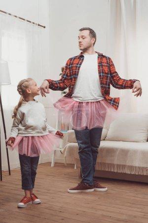 father and daughter in pink skirts
