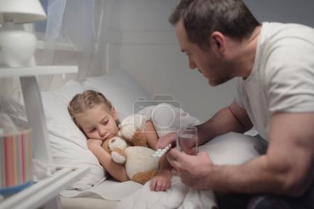 Photo pour Père tenant des pilules et un verre d'eau tout en regardant malade petite fille couchée dans le lit - image libre de droit