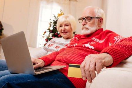 Photo pour Heureux couple senior avec carte de crédit et l'ordinateur portable, achats en ligne - image libre de droit