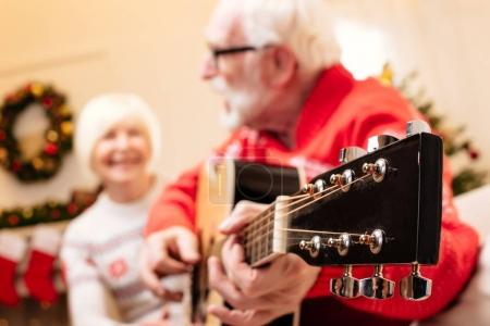 senior couple playing on guitar