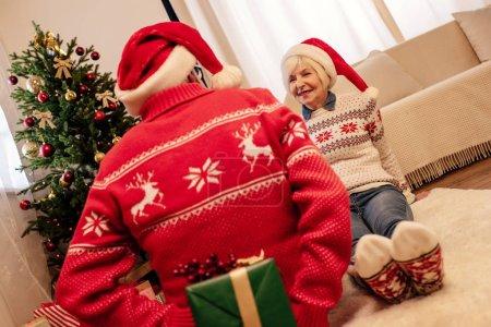 Foto de Senior hombre que sorpresa para la esposa en la víspera de Navidad - Imagen libre de derechos
