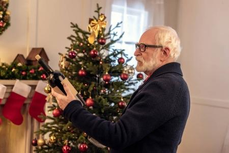 senior man with wine at christmastime