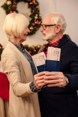 Photo pour Foyer sélectif de heureux couple de personnes âgées avec passeports et billets d'avion à la veille de Noël - image libre de droit