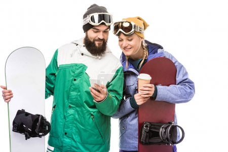 Couple with snowboards using smartphone