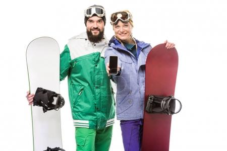 Couple with snowboards showing smartphone
