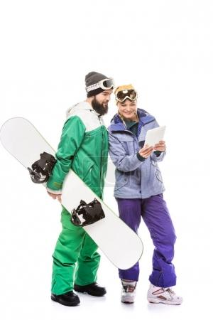 Couple of snowboarders with tablet