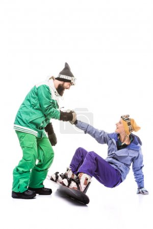 snowboarder helping girlfriend to get up