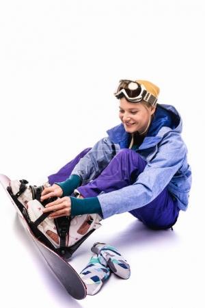 woman tying snowboard equipment