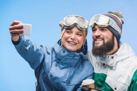 Photo pour Portrait de snowboardeurs gais prenant selfie sur smartphone ensemble isolé sur bleu - image libre de droit