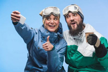Foto de Retrato de snowboarders alegres tomando selfie en smartphone junto aislada en azul - Imagen libre de derechos