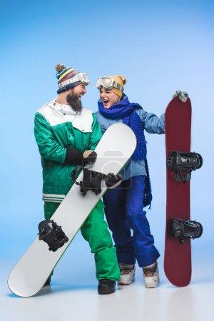 Photo pour Couple excité de snowboarders avec snowboards dans les mains isolées sur bleu - image libre de droit