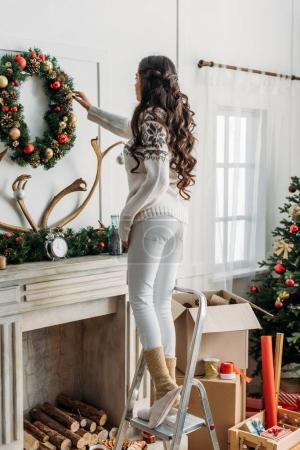 woman hanging christmas wreath over fireplace