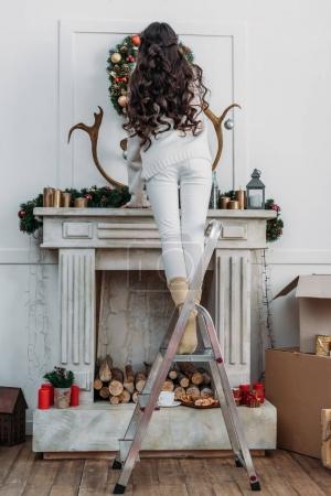 Photo pour Vue arrière de la femme suspendue couronne de Noël sur la cheminée tout en se tenant debout sur escabeau - image libre de droit