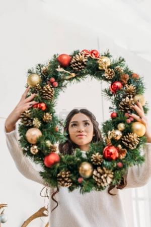 Photo for Young woman holding beautiful christmas wreath - Royalty Free Image