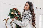 woman holding christmas wreath