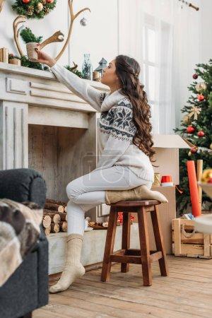 Photo pour Jeune femme décoration cheminée pour Noël tout en étant assis sur la chaise - image libre de droit