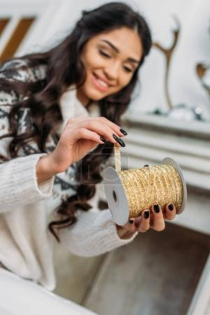 woman with coil of decorative ribbon