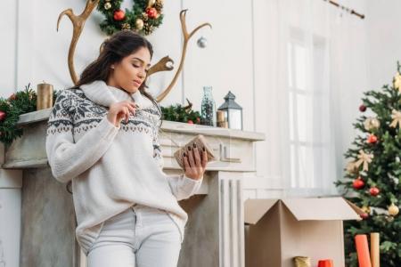 Photo pour Jeune femme avec bobine de fil se penchant sur cheminée à Noël décoration chambre - image libre de droit